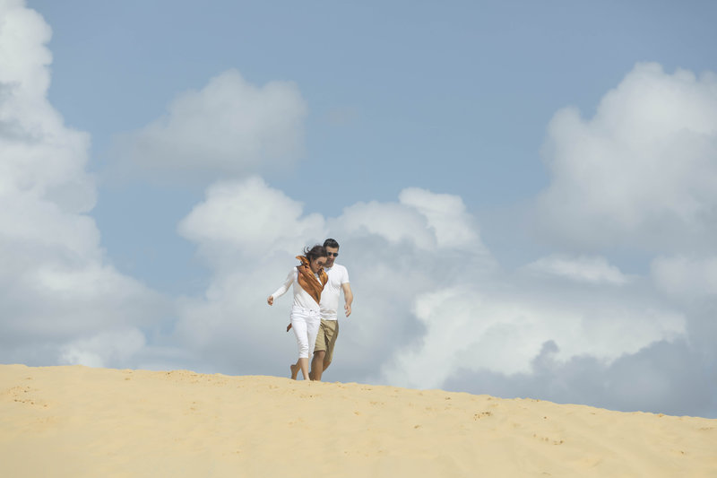 Couple walking on the red sand dunes